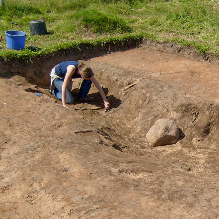 Archaeologist digging in the dunes at Bamburgh
